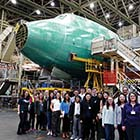 Group of people in front of an airplane under construction