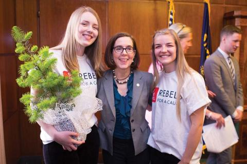 Rebels for a Cause students receiving a tree at the bill signing from the governor. Left to right: Rachel Mackley, Governor Kate Brown, Emma Monson.